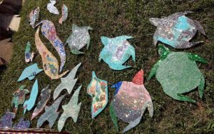 Children's painted critters drying in the sun.