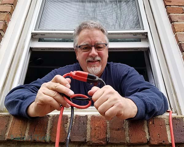 John handing me the light and the power cord through the bathroom window.