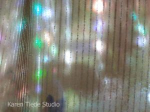 Rainbows from CD chains, projected against a sheer curtain.